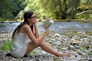 Girl reading at the creek